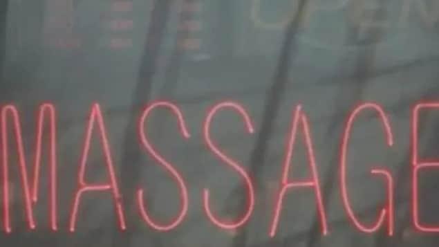 Gros plan du mot « massage » écrit en néon sur la fenêtre d'un salon.