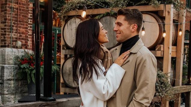 Un couple se regarde droit dans les yeux, en souriant, dans les rues de Toronto.