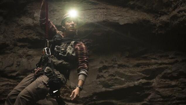 Samian, dans son rôle de jeune archéologue, est suspendu dans un énorme trou au moyen d'un harnais, s'éclairant à l'aide d'une lampe frontale.