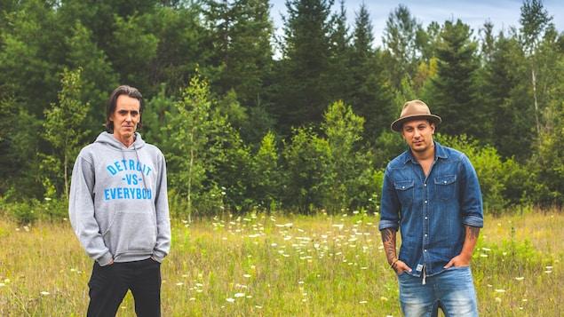 Les deux hommes sont debout dans une prairie.