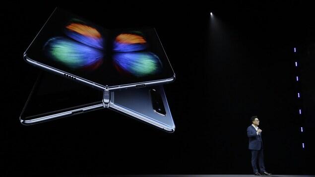 Une photo du président de Samsung, DJ Koh, sur une scène devant une écran géant montrant le téléphone Galaxy Fold.