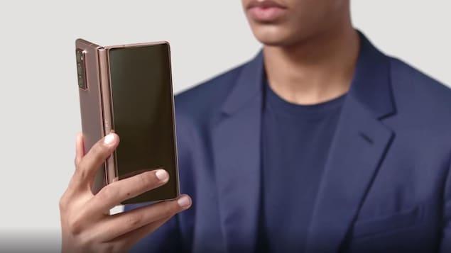 Un homme en complet tient le téléphone pliable Samsung Galaxy Z Fold 2.