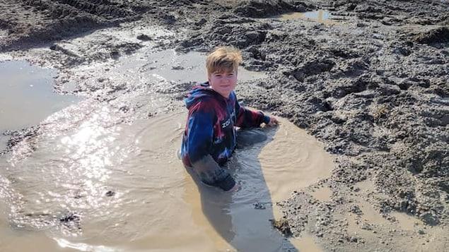 Samuel Desjardins plongé jusqu'à la taille dans un trou d'eau boueuse.
