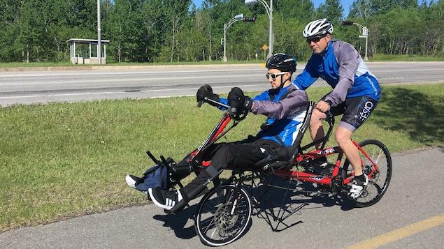 Deux hommes sont sur un vélo et roulent sur une piste cyclable.