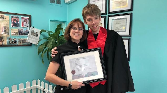 Annie Perron et Samuel Ouellet enlacés pour prendre une photo officielle avec le diplôme d'aide-toiletteur.