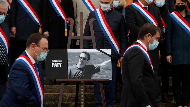Des députés entourant le portrait de Samuel Paty sur les marches du Palais-Bourbon.