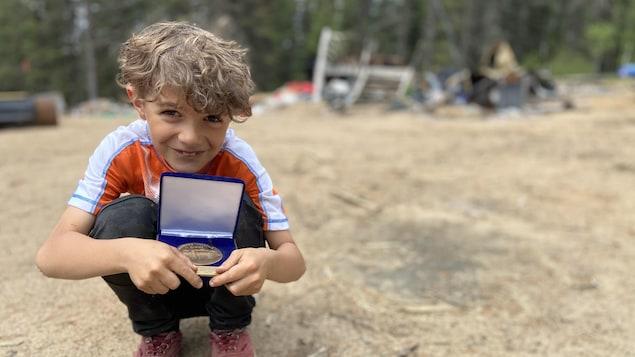 Samuel accroupi et montrant sa médaille.