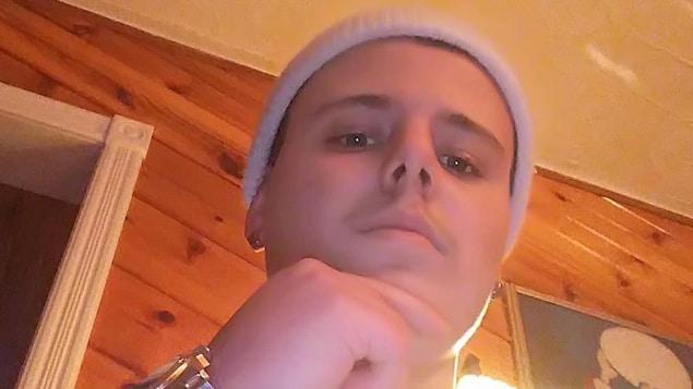 Gros plan d'un jeune homme qui porte un bonnet et des boucles d'oreilles.