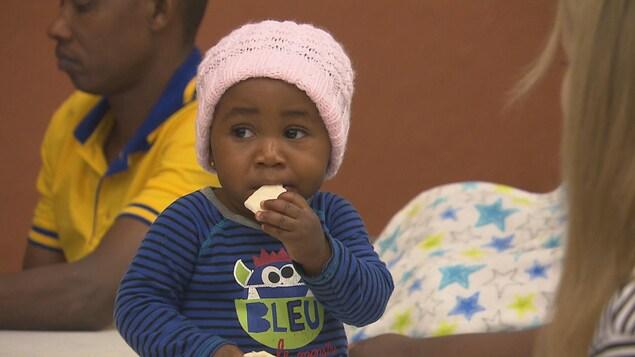 Un enfant mange un morceau de pain lors de la fête de Noël du Sana de Trois-Rivières.