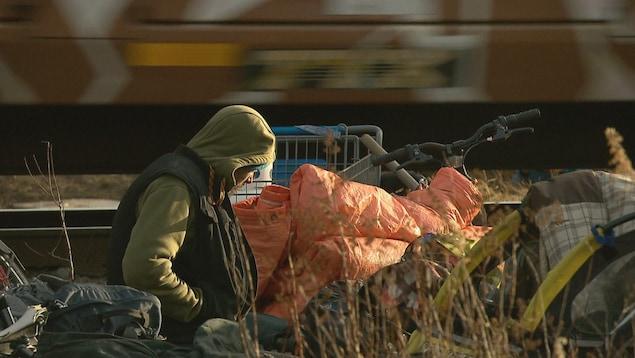 Un itinérant est assis en bordure d'une voie ferrée, son visage est dissimulé par la capuche de son blouson.