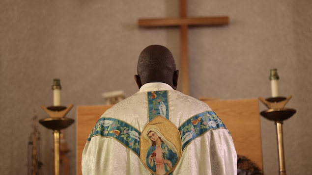 Un prêtre africain de dos devant un autel avec une croix en arrière plan.