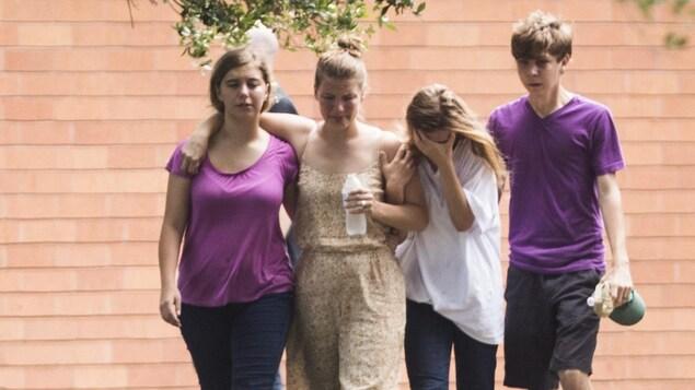 Quatre adolescents marchent ensemble dans l'herbe, l'air attristé. Certains semblent pleurer.