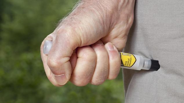 Une personne utilise un auto-injecteur EpiPen.