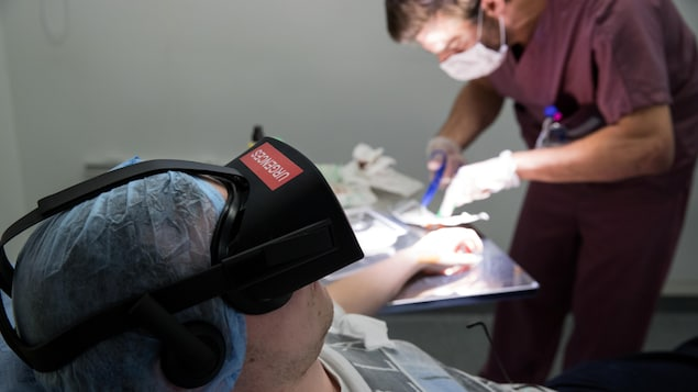 A nurse treats a patient wearing the 3D therapeutic virtual reality headset developped by Healthy Mind start-up, at the emergency service department of the Saint-Joseph Hospital in Paris, France, June 7, 2018. The headset immerses the patient in the heart of a Zen garden or an enchanted forest to counter the pain rather than increase the doses of painkillers. Picture taken June 7, 2018.   REUTERS/Philippe Wojazer - RC1AFB9B4880