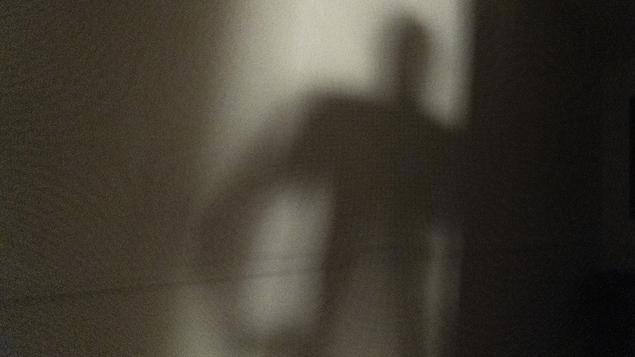 La silhouette d'un homme se dessine dans le cadre d'une porte