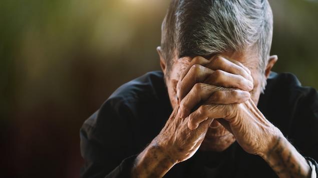 Un homme cache son visage avec des mains en prière.
