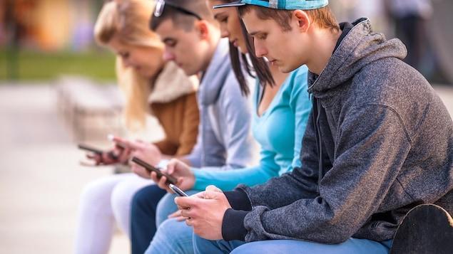 Un groupe d'adolescents assis à l'extérieur regardent leurs téléphones cellulaires.