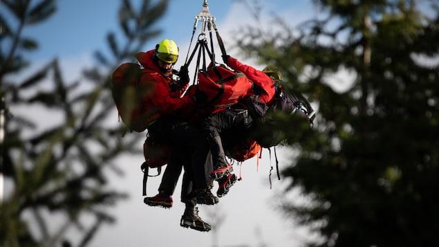 Des secouristes avec de l'équipement pendent d'un hélicoptère.