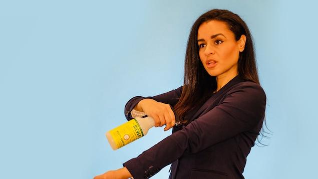 Une femme tient un vaporisateur contenant du désinfectant et le pointe vers le pli intérieur de son coude.