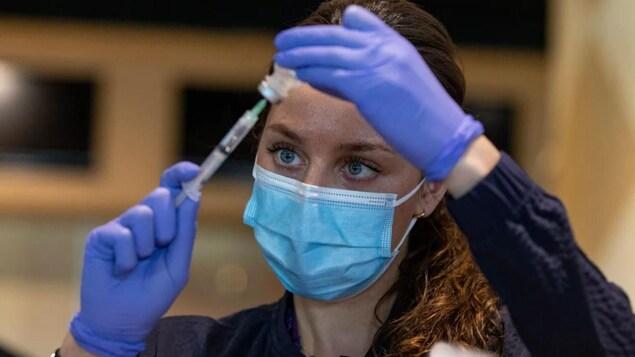 Une infirmière prépare une dose de vaccin contre la COVID-19.