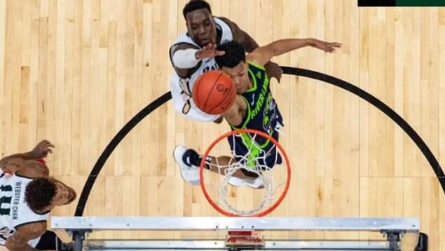 Un joueur de basketball est sur le point de déposer le ballon dans le panier.