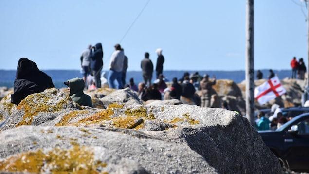 Des gens près des rochers. Un drapeau mi'kmaq flotte.