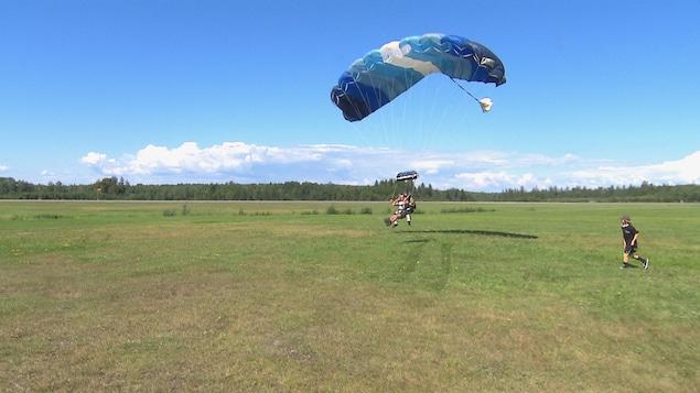 Des parachutistes atterrissent au sol.