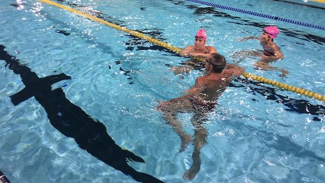 Deux femmes et un homme dans une piscine