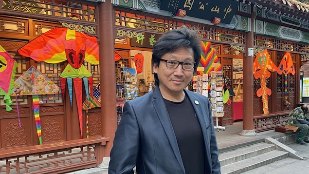 Portrait de Jimmy Chan debout devant une pagode décorée.