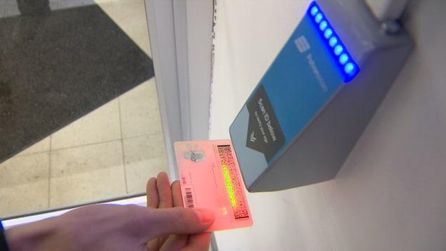 Un permis de conduire est scanné par un dispositif à l'entrée d'un magasin.