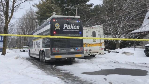 Des véhicules de police sur une rue résidentielle, en hiver.