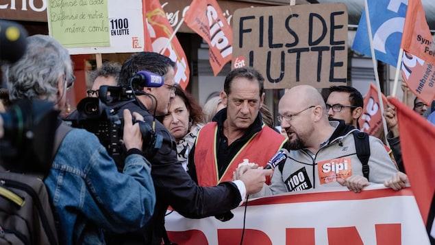 Des hommes tiennent un banderole alors que d'autres brandissent des pancartes derrière eux. Un homme répond au micro d'un journaliste.