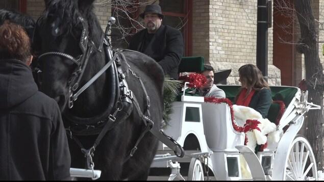 Une calèche tirée par deux chevaux noirs. Un homme et une femme prennent place dans la calèche.