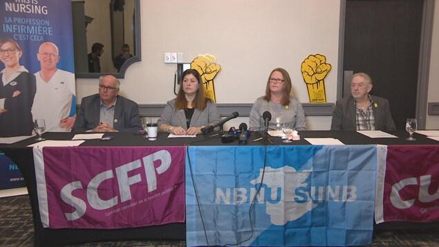 Les représentants syndicaux sont assis à une table avec des micros pour donner une conférence de presse.
