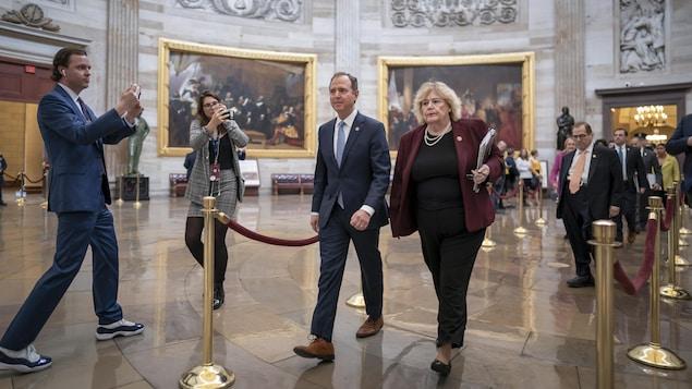 Les responsables de la mise en accusation, dont Adam Schiff et Zoe Lofgren à l'avant-plan, marchent dans les couloirs du Capitole, sous l'œil des caméras.