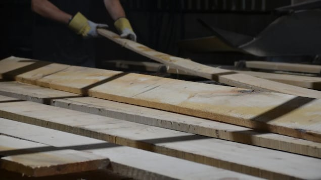 Un ouvrier manipule des planches dans une scierie.