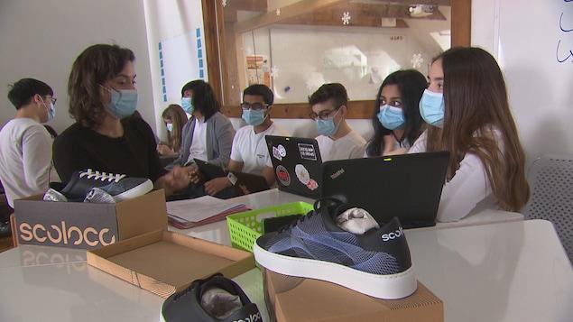Des chaussures sont posées sur une table. Des élèves sont assis tout près, portant des masques, certains avec des ordinateurs portables.