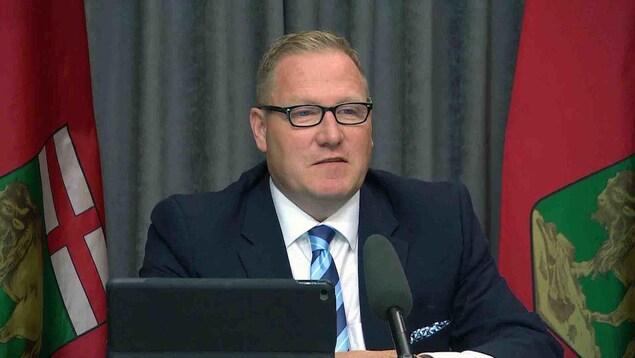Le ministre des Finances du Manitoba, Scott Fielding, assis à un bureau.