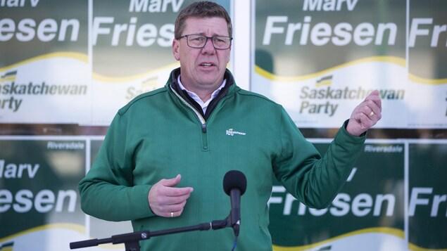 Scott Moe est en train de parler au micro devant des affiches de la candidate Mary Friesen.