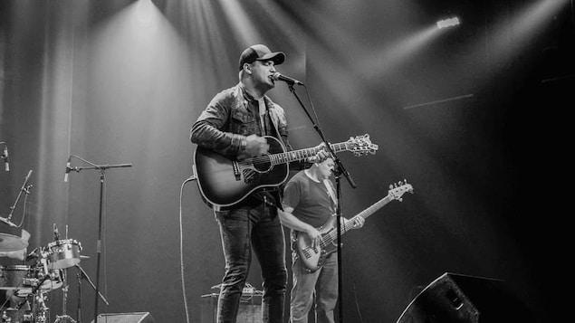 Le chanteur est sur scène avec sa guitar.
