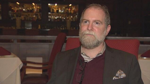 Scott Winograd, le copropriétaire du restaurant Bear's Den, est assis sur une chaise rouge dans son restaurant.