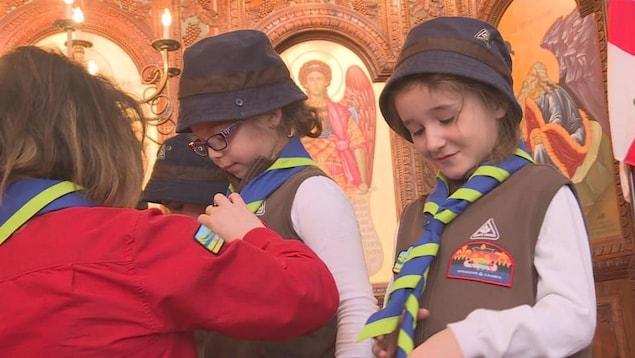 Une fillette en habit de scout regarde fièrement son foulard vert et bleu.
