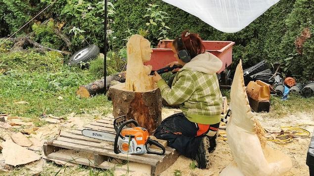 Une sculptrice taille un visage dans du bois.