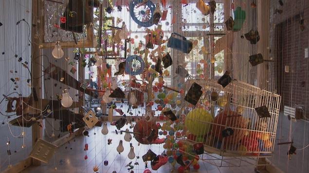 Une sculpture suspendue dans un local. On y voit des objets attachés à des ficelles.