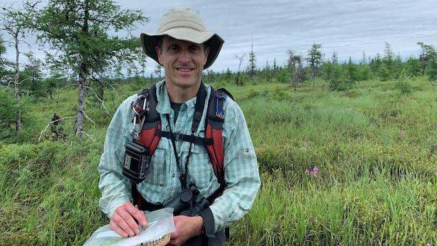 Sean Blaney vêtu de son équipement de recherche tient des outils dans ses mains. Il est photographié dans les herbes hautes de la tourbière d'Alward Brook.