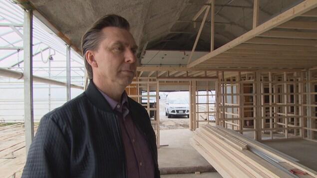 Un homme dans une serre en construction.