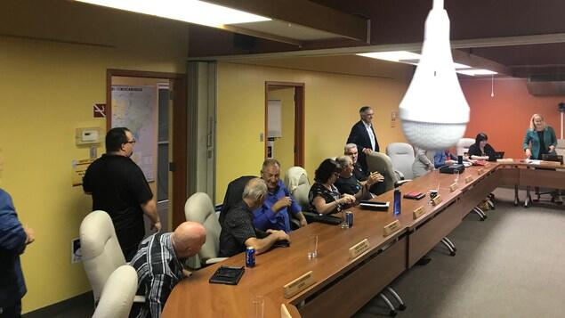 Les élus prennent place dans la salle du conseil où sont installés des micros au plafond.