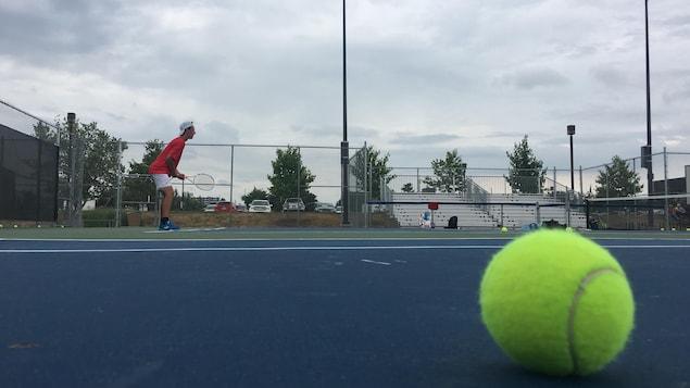 Un joueur de tennis attend un service, une balle à l'avant-plan.