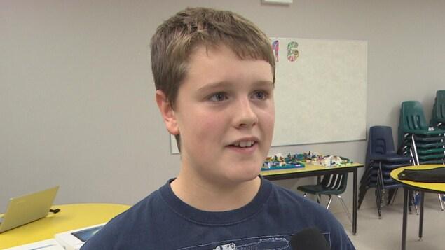 Un jeune garçon aux cheveux courts s'exprime au micro du journaliste.