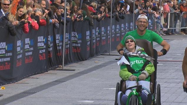 Le pédiatre Sébastien Roulier qui pousse une personne handicapée dans un chariot.